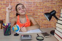 Muchacha sonriente del adolescente que hace la preparación en la tabla en casa Estudiante con la pila de libros y de notas que es Fotografía de archivo