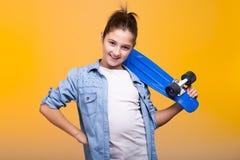 Muchacha sonriente del adolescente que mira la cámara y sostener un patín azul Fotografía de archivo