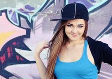 Muchacha sonriente del adolescente que presenta cerca de la pared Imagen de archivo