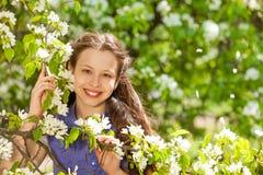 Muchacha sonriente del adolescente que sostiene las flores blancas de la pera Fotos de archivo