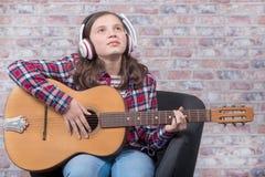 Muchacha sonriente del adolescente que toca la guitarra acústica Imágenes de archivo libres de regalías