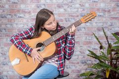Muchacha sonriente del adolescente que toca la guitarra acústica Fotos de archivo libres de regalías