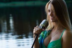 Muchacha sonriente del cantante del adolescente con el micrófono retro Foto de archivo libre de regalías