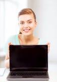 Muchacha sonriente del estudiante con el ordenador portátil Fotos de archivo libres de regalías