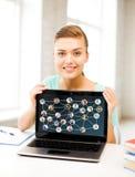 Muchacha sonriente del estudiante con el ordenador portátil en la escuela Fotografía de archivo