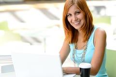 Muchacha sonriente del estudiante con el ordenador portátil en la universidad Imágenes de archivo libres de regalías