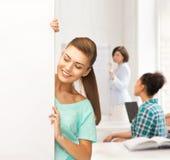 Muchacha sonriente del estudiante con el tablero en blanco blanco Fotografía de archivo