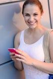 Muchacha sonriente del estudiante con el teléfono móvil Fotos de archivo libres de regalías