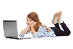 Muchacha sonriente del estudiante con la mentira del ordenador portátil Imagenes de archivo