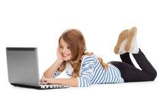 Muchacha sonriente del estudiante con la mentira del ordenador portátil Imagen de archivo libre de regalías