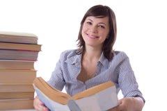 Muchacha sonriente del estudiante con la pila de libros Foto de archivo libre de regalías