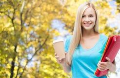 Muchacha sonriente del estudiante con las carpetas y la taza de café Foto de archivo