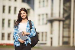 Muchacha sonriente del estudiante con los libros y la mochila que se colocan en univers Fotos de archivo libres de regalías