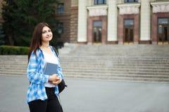 Muchacha sonriente del estudiante con los libros y la mochila que se colocan en univers Imagenes de archivo