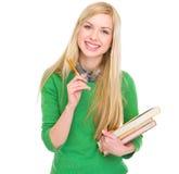 Muchacha sonriente del estudiante con los libros y la pluma Foto de archivo libre de regalías