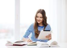 Muchacha sonriente del estudiante con PC y los libros de la tableta Fotografía de archivo libre de regalías