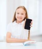 Muchacha sonriente del estudiante con smartphone en la escuela Foto de archivo libre de regalías