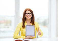 Muchacha sonriente del estudiante en eyelgasses con PC de la tableta Imagen de archivo libre de regalías