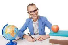 Muchacha sonriente del estudiante en libros de lectura de las lentes Imagen de archivo libre de regalías
