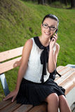 Muchacha sonriente del estudiante que habla en el teléfono móvil Fotos de archivo libres de regalías