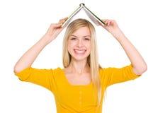 Muchacha sonriente del estudiante que hace el tejado con el libro Fotografía de archivo