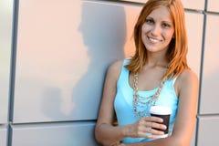 Muchacha sonriente del estudiante que lleva a cabo verano de la taza de café Fotografía de archivo libre de regalías