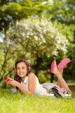 Muchacha sonriente del estudiante que miente en parque del verano Fotografía de archivo