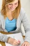 Muchacha sonriente del estudiante que mira la escritura en el papel Foto de archivo