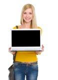 Muchacha sonriente del estudiante que muestra la computadora portátil Fotografía de archivo libre de regalías