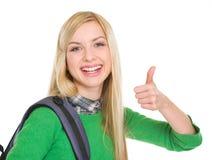 Muchacha sonriente del estudiante que muestra los pulgares para arriba Imagen de archivo libre de regalías