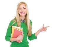 Muchacha sonriente del estudiante que señala en espacio de la copia Fotos de archivo