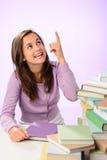 Muchacha sonriente del estudiante que señala encima de fondo púrpura Imagen de archivo libre de regalías