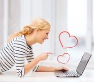 Muchacha sonriente del estudiante que señala su finger en el ordenador portátil Fotos de archivo libres de regalías