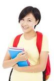 Muchacha sonriente del estudiante que se coloca sobre el fondo blanco Foto de archivo libre de regalías