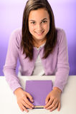 Muchacha sonriente del estudiante que se sienta detrás de púrpura del escritorio Foto de archivo