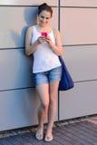 Muchacha sonriente del estudiante que usa la universidad del teléfono móvil Imagenes de archivo
