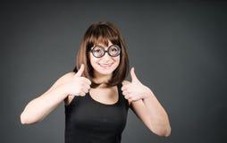 Muchacha sonriente del friki en vidrios con los pulgares para arriba Mujer feliz del empollón del ganador Foto de archivo