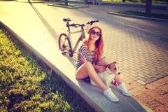 Muchacha sonriente del inconformista con el animal doméstico y la bici en verano Imagen de archivo libre de regalías