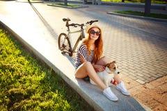 Muchacha sonriente del inconformista con el animal doméstico y la bici en verano Fotos de archivo