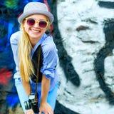 Muchacha sonriente del inconformista con la cámara retra de la foto contra Foto de archivo