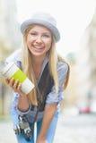 Muchacha sonriente del inconformista con la taza de bebida caliente en la calle de la ciudad Foto de archivo libre de regalías