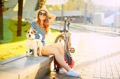 Muchacha sonriente del inconformista con su perro en ciudad del verano Imagen de archivo