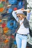 Muchacha sonriente del inconformista contra la pared urbana Fotografía de archivo