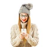 Muchacha sonriente del inconformista del invierno adentro con el teléfono móvil en blanco Foto de archivo libre de regalías