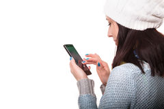 Muchacha sonriente del inconformista del invierno en suéter y Beanie Hat hechos punto con el teléfono móvil aislado en blanco Com Fotos de archivo libres de regalías