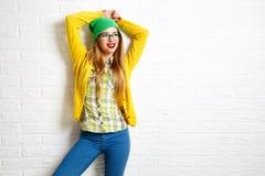 Muchacha sonriente del inconformista en el fondo blanco de la pared de ladrillo Foto de archivo libre de regalías