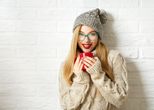 Muchacha sonriente del inconformista en ropa del invierno con la taza Imagen de archivo