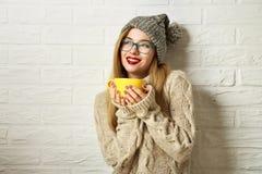 Muchacha sonriente del inconformista en ropa del invierno con una taza Imagen de archivo libre de regalías