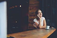 Muchacha sonriente del inconformista que llama con el teléfono de célula mientras que se relaja después de caminar en día de vera Foto de archivo