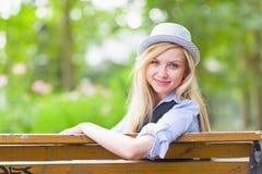 Muchacha sonriente del inconformista que se sienta en banco en el parque de la ciudad Fotos de archivo